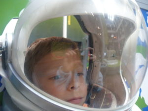 Image of child in spacesuit helmet with Dolly the sheep reflected in the background